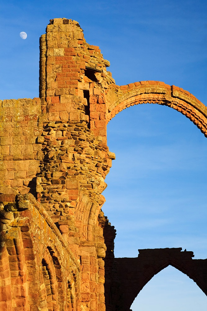 The moon framed by the remains of Lindisfarne Priory, Holy Island, Northumberland