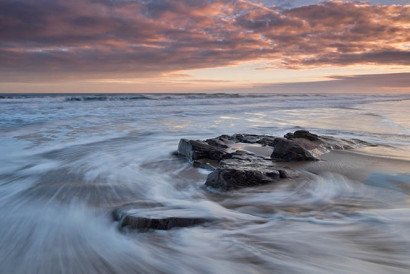 Water swirling around a rock on Cheswick Sands beach, Northumberland, England